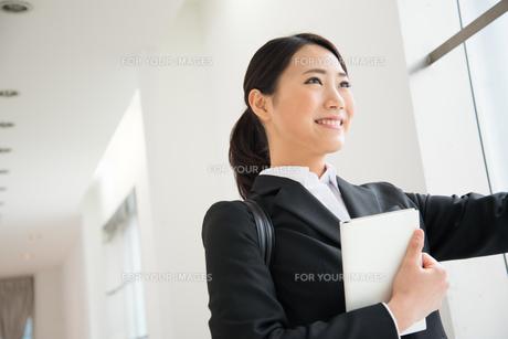 スケジュール帳を持っているスーツ姿の女性 FYI01078610