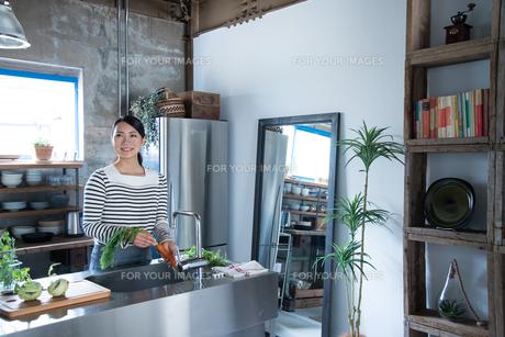 キッチンで野菜を洗っている女性の素材 [FYI01078611]