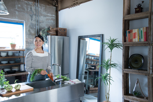 キッチンで野菜を洗っている女性 FYI01078611