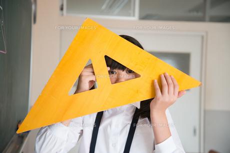 黒板の前で三角定規を持っている小学生の女の子 FYI01078621