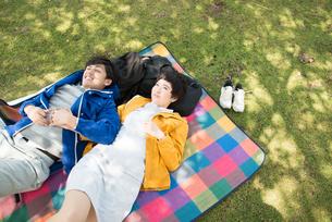 ピクニックマットの上に寝転がる男女 FYI01078632