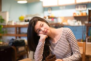 カフェで頬杖をついている女性 FYI01078635