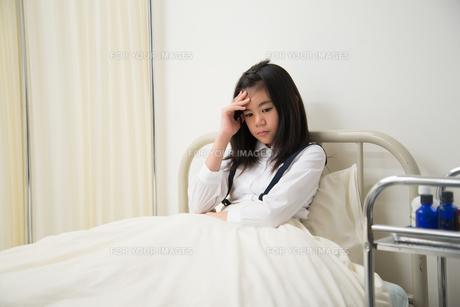 保健室のベッドにいる具合の悪そうな小学生の女の子 FYI01078638