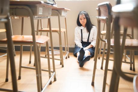 教室の床に座っている小学生の女の子 FYI01078674