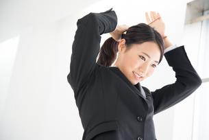 髪を結んでいるスーツ姿の女性 FYI01078682