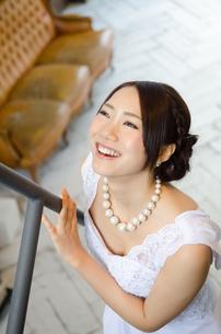 手すりを触りながら笑うドレス姿の女性 FYI01078691