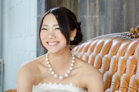 白いドレスを着てソファに座る女性の素材 [FYI01078695]