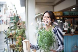 お花の鉢を持って笑っている女性 FYI01078710