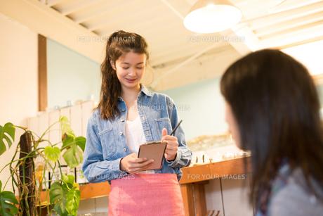 カフェで注文を取っている女性 FYI01078719