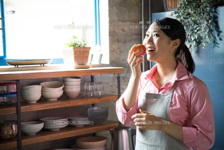 キッチンでりんごを食べようとしている女性 FYI01078736
