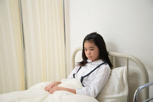 保健室のベッドにいる小学生の女の子 FYI01078752