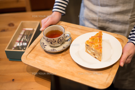 ケーキと紅茶が載っているトレイを持っている女性の手 FYI01078754