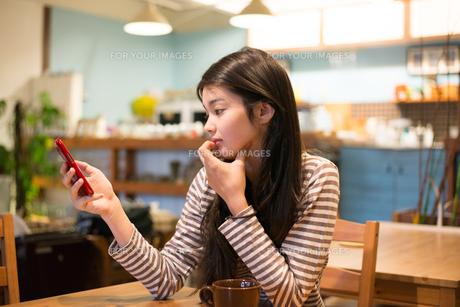 カフェで携帯を見ている女性 FYI01078757