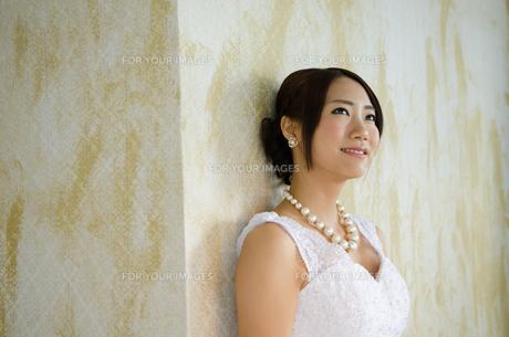 壁にもたれるドレス姿の女性 FYI01078765
