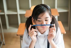 鼻の下に鉛筆を挟んでいる小学生の女の子 FYI01078771