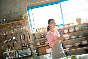 キチンでお皿を持っている女性 FYI01078772