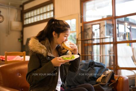 カフェでサンドイッチを食べている女性の素材 [FYI01078776]