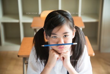 鼻の下に鉛筆を挟んでいる小学生の女の子 FYI01078800