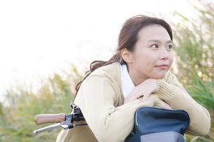 自転車のハンドルにもたれる女子学生 FYI01078824