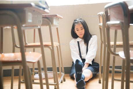 教室の床に座っている小学生の女の子 FYI01078826