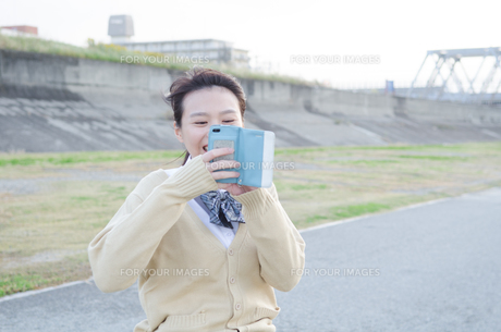 スマホで写真を撮っている女子学生 FYI01078835