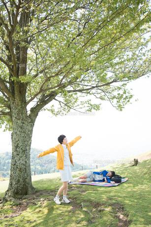 木の下で深呼吸をする女性と寝転がる男性 FYI01078861