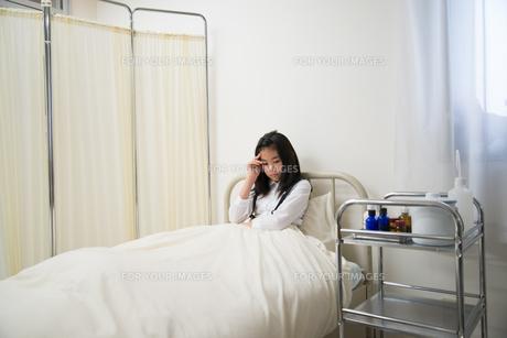 保健室のベッドにいる具合の悪そうな小学生の女の子 FYI01078884