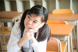 頬杖をついている小学生の女の子 FYI01078891