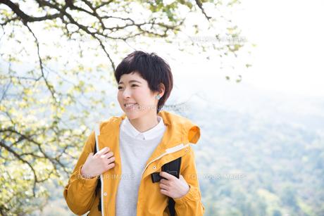木をバックに笑っている女性 FYI01078999