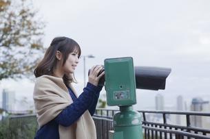 展望台から双眼鏡で神戸の景色を望む笑顔の女性 FYI01096541
