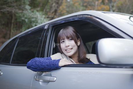 秋の紅葉の公園の駐車場で車の運転をする女性 FYI01096556