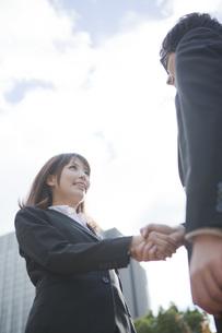 ビルの前で握手をするビジネスウーマンとビジネスマン FYI01096558