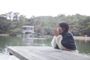 公園のテーブルに肘を付くニットセーターを着た女性 FYI01096602