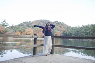 秋の紅葉の公園の池のほとりで伸びをする女性 FYI01096619