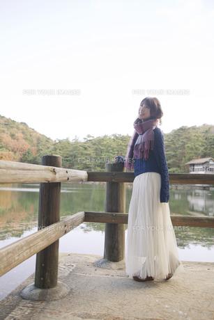 秋の紅葉の公園の池のほとりで池を見つめる女性 FYI01096622