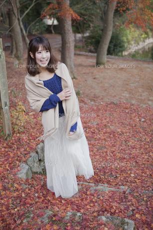 秋の紅葉の落ち葉の上の階段を歩く笑顔の女性 FYI01096652