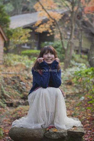 秋の紅葉の公園で座っている笑顔の女性 FYI01096653