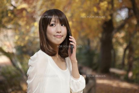 秋の紅葉した公園で立って携帯電話を掛けている女性 FYI01096654