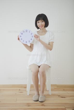 椅子に座って時計を持つ女性 FYI01096663