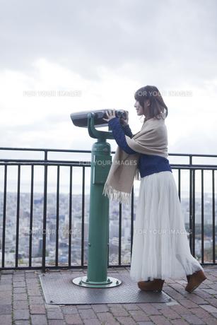 展望台から双眼鏡で神戸の景色を望む笑顔の女性 FYI01096676
