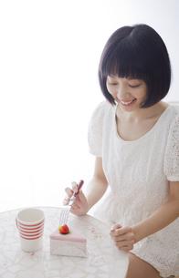 テーブルとおもちゃのケーキセットと女性 FYI01096722