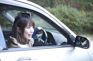 秋の紅葉の公園の駐車場で車の運転をする女性 FYI01096735