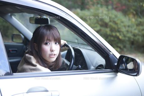 秋の紅葉の公園の駐車場で車の運転をする女性 FYI01096739