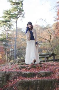秋の紅葉の落ち葉の上の階段を歩く笑顔の女性 FYI01096741
