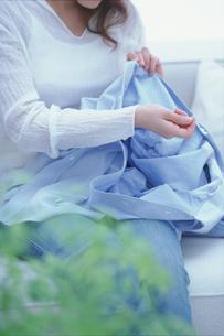 水色のシャツを繕う女性 FYI01121152