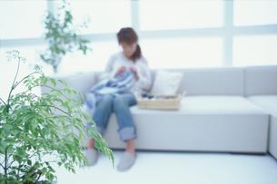 ソファで針仕事をする女性のシルエット FYI01121267
