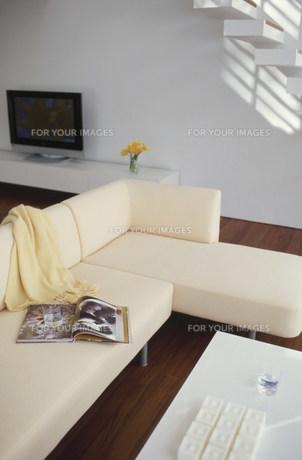 膝掛けや雑誌を置いたソファとテレビのある部屋 FYI01122399
