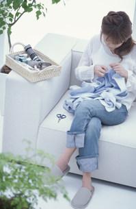 ソファに座って裁縫をする女性 FYI01122413