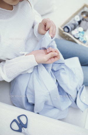 ソファに座って裁縫をする女性 FYI01122477