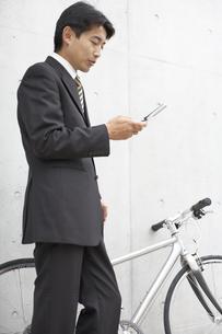 携帯電話を見るビジネスマンと自転車 FYI01129355